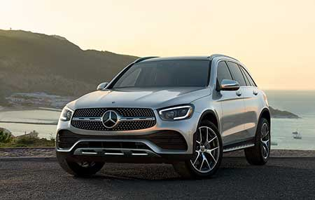 A silver Mercedes-Benz cabriolet is parked with the top down in front of a row of modern windmills.