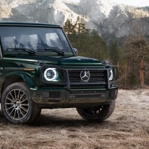 Display A rugged Mercedes-Benz G-Class SUV parked in a forest clearing with mountains in the background.
