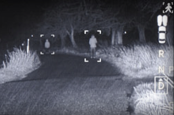 A black and white night-vision view of a road with people standing on the shoulder.