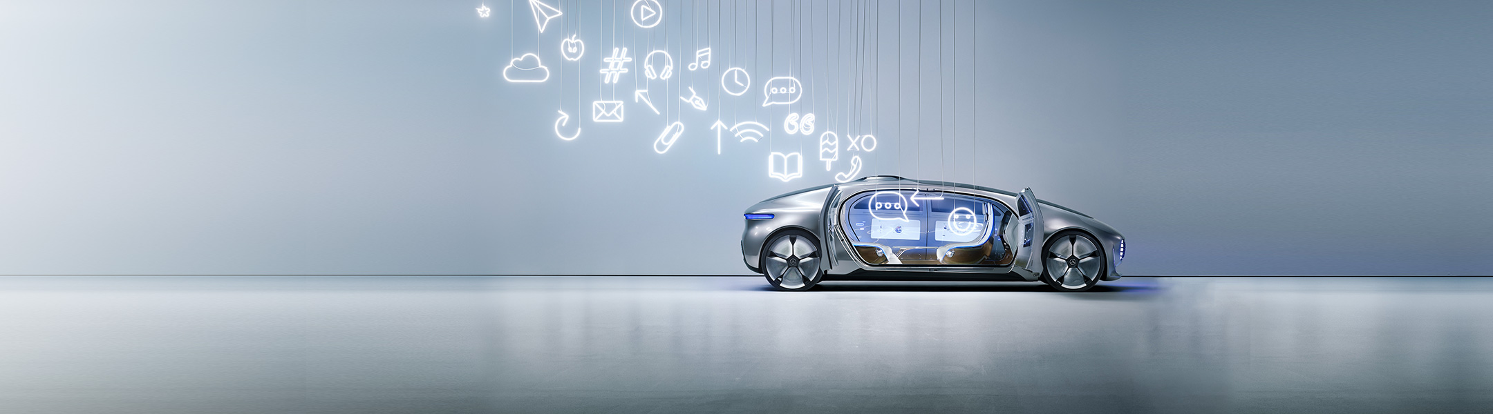 The autonomous Luxury in Motion sits with doors open as electric icons dangle above it.